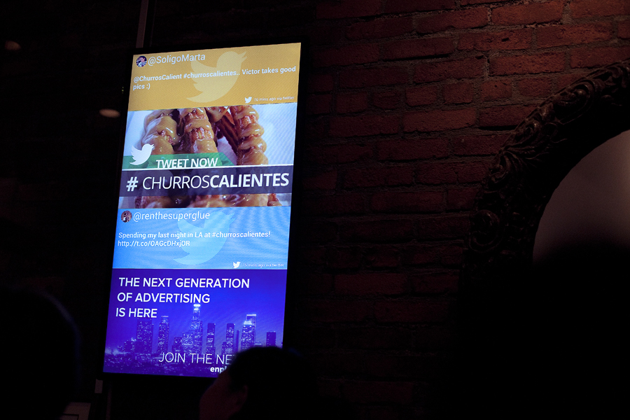 Marta and Ren's tweets tagged #churroscalientes on display at a digital screen in Churros Calientes.
