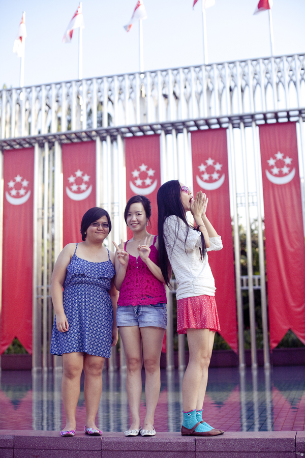 Puey, Ade, and Ren in front of Singapore flags.