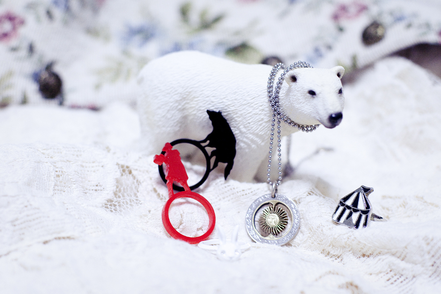 Closeup of accessories and my polar bear. Lickety Cut Red Riding Hood acrylic ring set, Redone Argentine coin necklace, white bunny ring, circus tent ring.