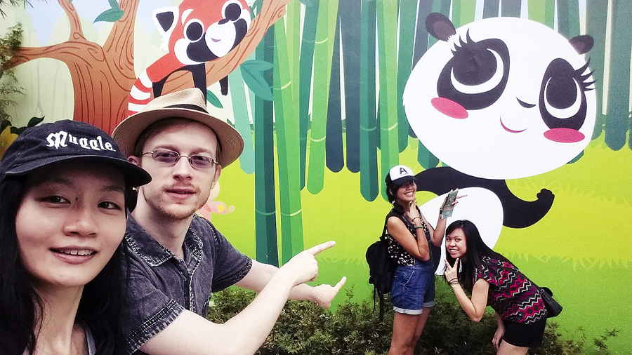 Friends and I in front of a stylised panda wall at the River Safari.