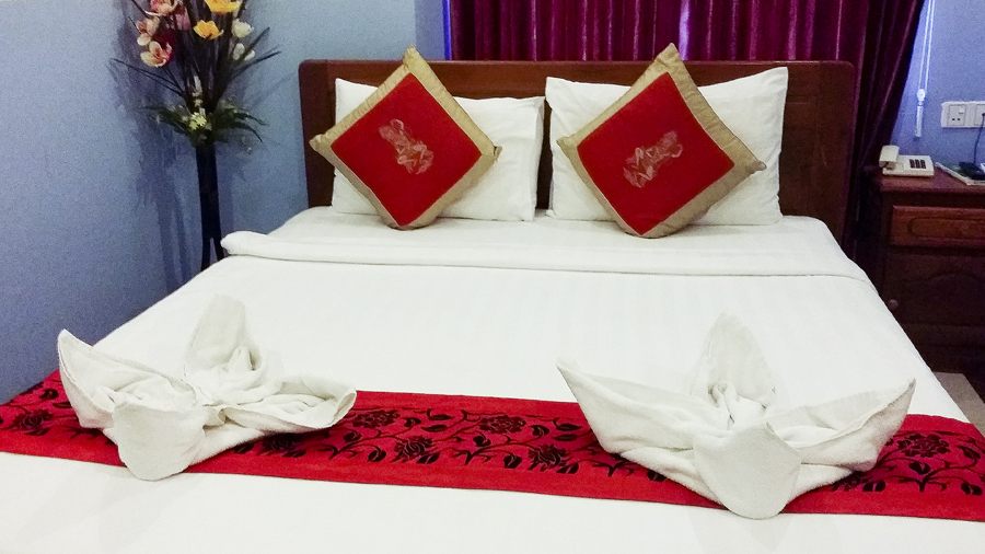 Queen bed at the Queen Wood Hotel in Phnom Penh, Cambodia.