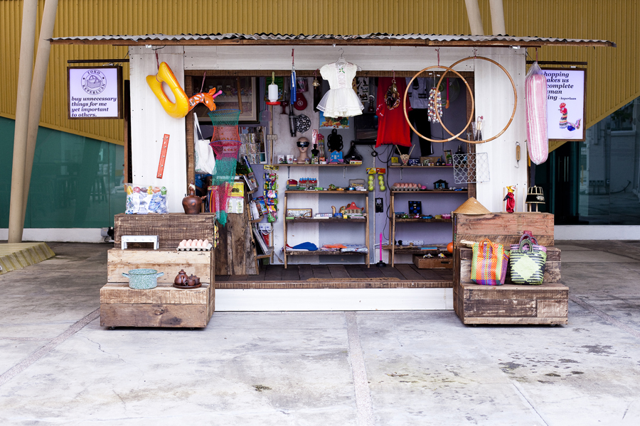 Toko Keperluan by Anggun Priambodo. Installation with wooden shop, consumer items, video and performance.