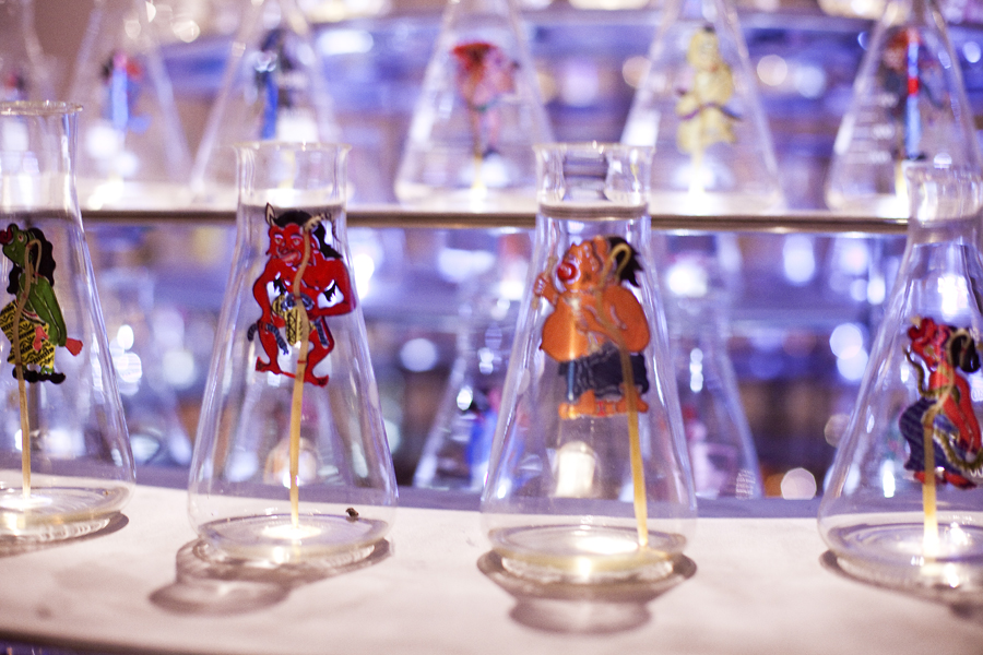 Detail of Between Worlds by Nasirun. An installation with leather puppets in glass bottles.