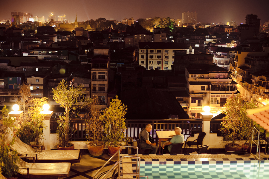 View of pool deck of the Queen Wood Hotel, and the night skyline in Phnom Penh, Cambodia.