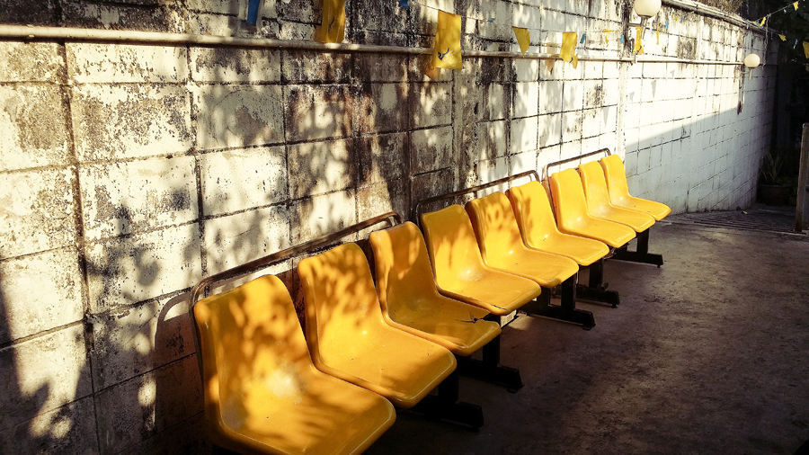 Yellow chairs by the dock at Chao Phraya River in Bangkok, Thailand.