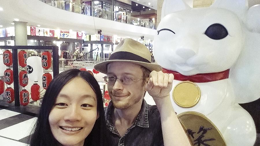 Ren and Ottie posing with a Maneki Neko fortune cat statue in Terminal 21 in Bangkok, Thailand.