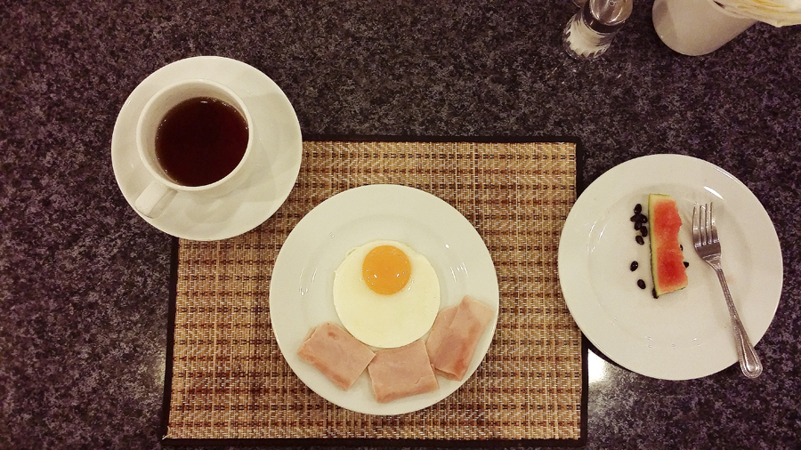 Breakfast of eggs and ham at Vieng Tai Hotel in Bangkok, Thailand.