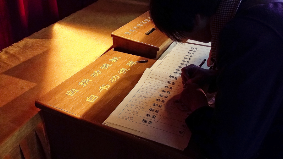 Writing down a name after donating to the temple at Jing'An temple, Shanghai.