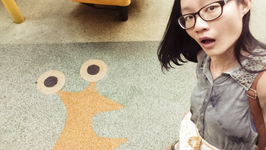 Ren posing with a picture of a snail on the ground of a playground.