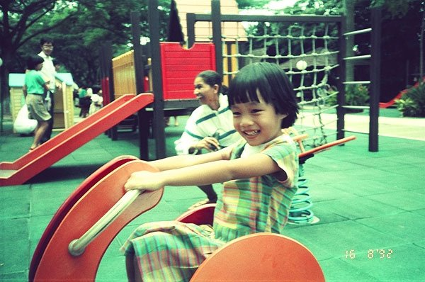 Childhood photo of Ren on a rocking horse.