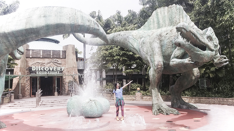 Posing with dinosaur sculptures at Jurassic Park at Universal Studios Singapore.