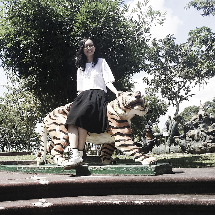 Ren sitting on a statue of a tiger at Haw Par Villa, Singapore.