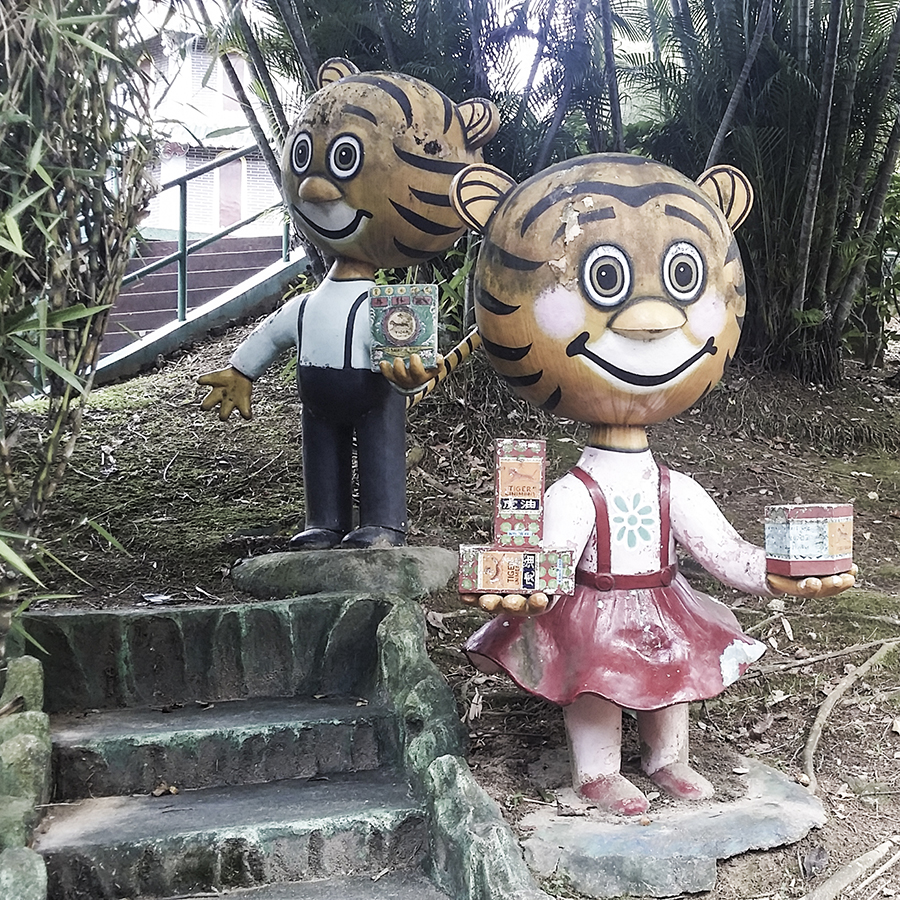Cute tigers holding Tiger Balm products at Haw Par Villa, Singapore.