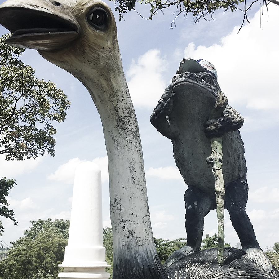 Forg in baseball cap perched atop an ostrich at Haw Par Villa, Singapore.