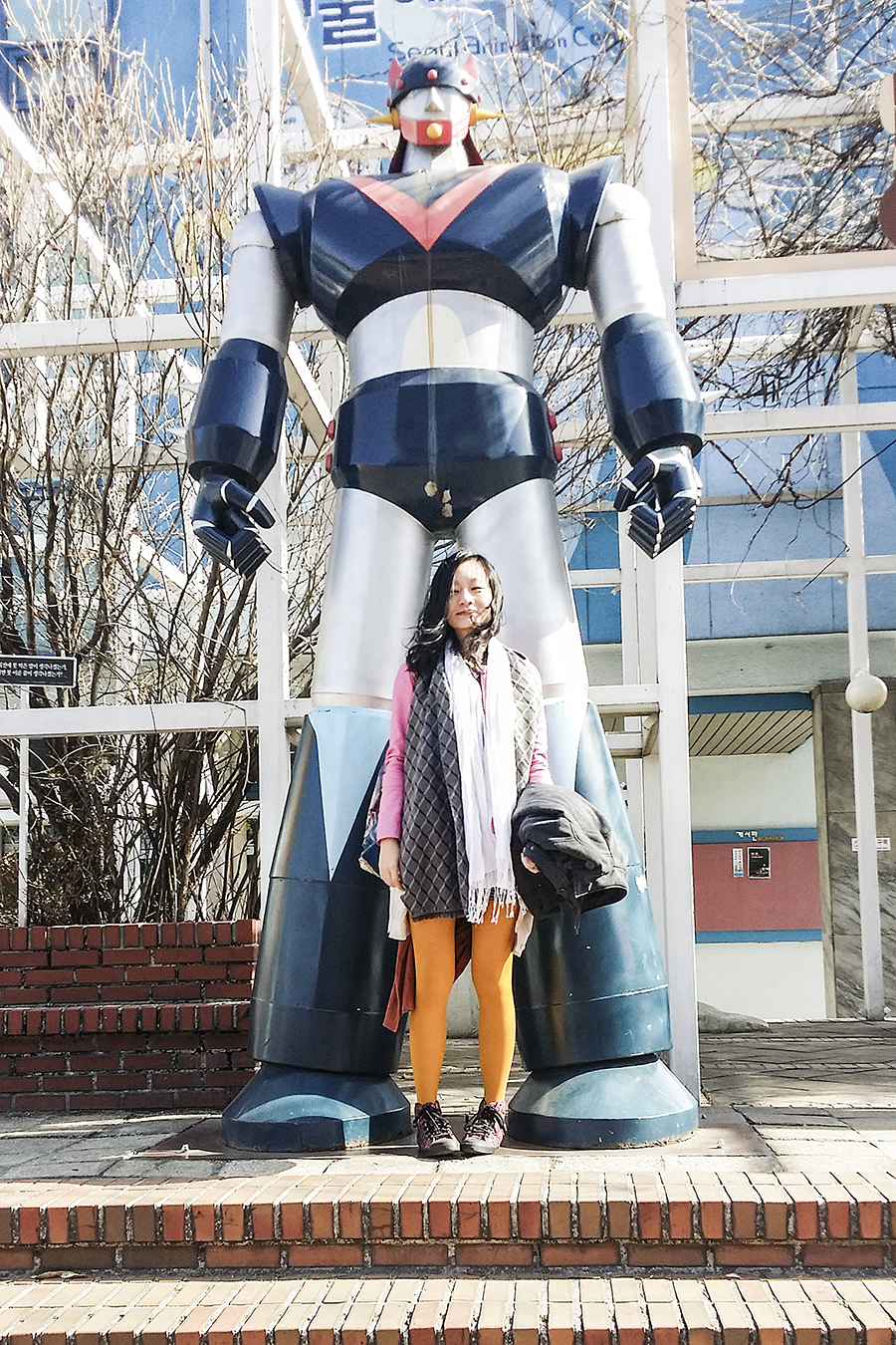 Posing with giant robot sculpture at Seoul Animation Center, South Korea.
