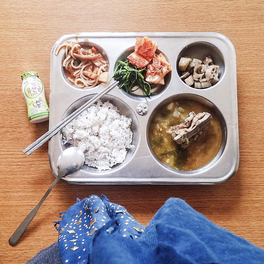 School lunch: probiotic drink, kimchi, lotus roots, pork ribs, spinach, steamed rice.