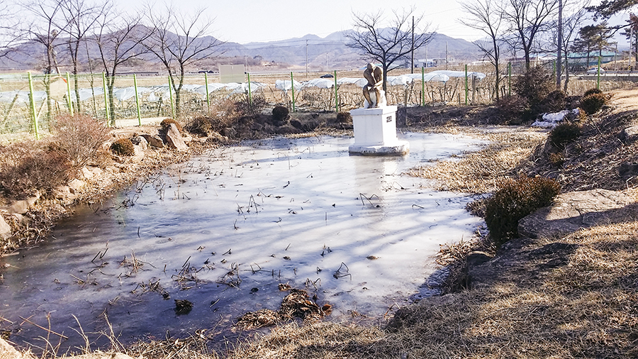 Pond frozen over with a Thinker statue in the middle in the school in the mountain, Sangju, South Korea.