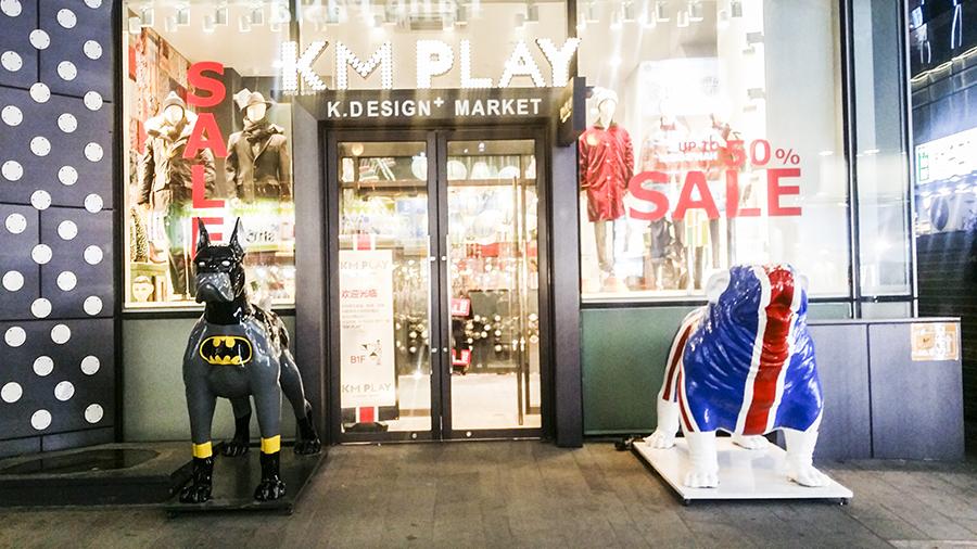 Cute batman-painted doberman statue and Union Jack flag bulldog statue outside a store in Myeongdong, Seoul, South Korea.