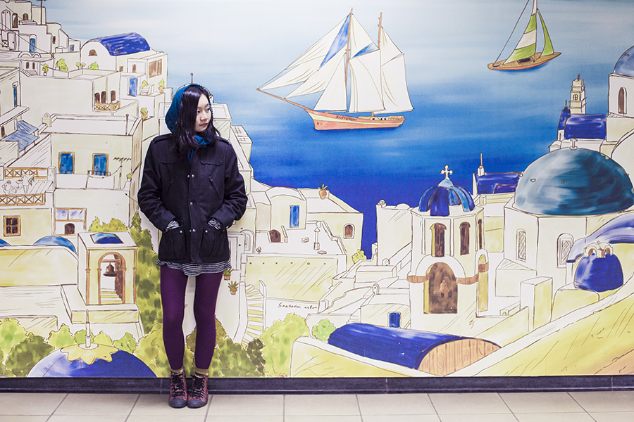 Outfit in front of a mural of Santorini, Greece on Seoul subway station, South Korea: H&M grey men's jacket, Marshalls gold studded shawl, Zara striped dress, Hue ribbed tights, Alexander McQueen x Puma red sneakers.