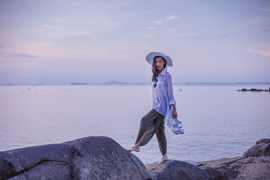 Climbing rocks by the sea at Turi Beach Resort, Batam, Indonesia. Wearing: Ralph Polo mermaid bikini top, M)phosis sheer white chiffon blouse, H&M white beach hat, Haute Hippie slit drape pants in olive green, Taobao white platform sandals, 24:01 round sunglasses via Zalora.