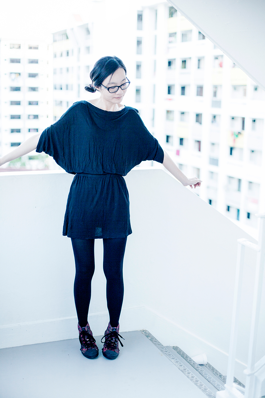 Monochroma outfit: M)phosis black tunic dress, Alexander McQueen x Puma high top sneakers, Gap black frame glasses.