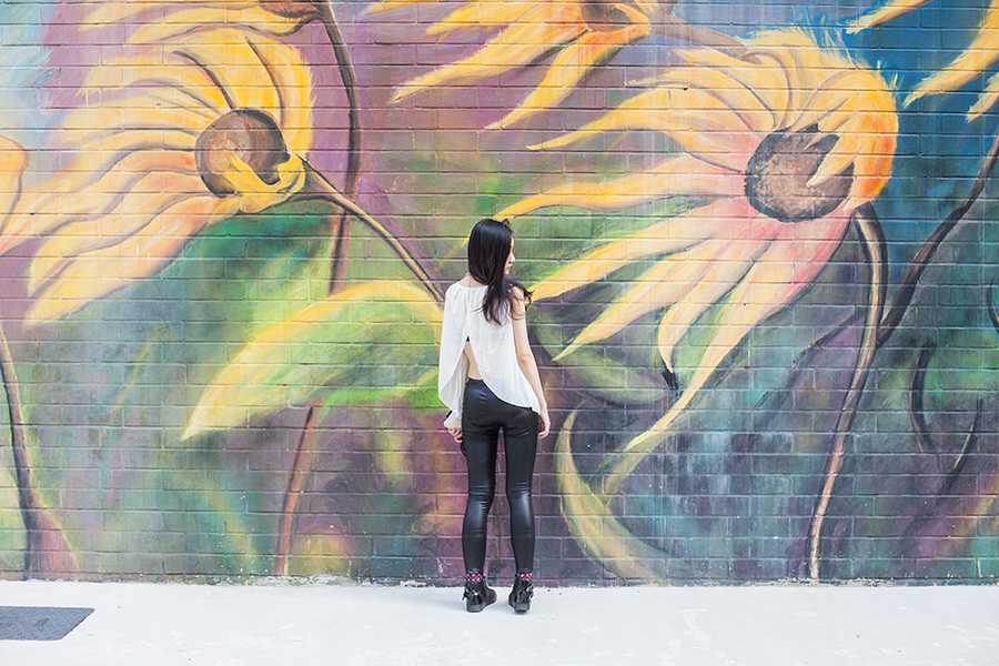 Monochrome chic outfit against sunflower mural.