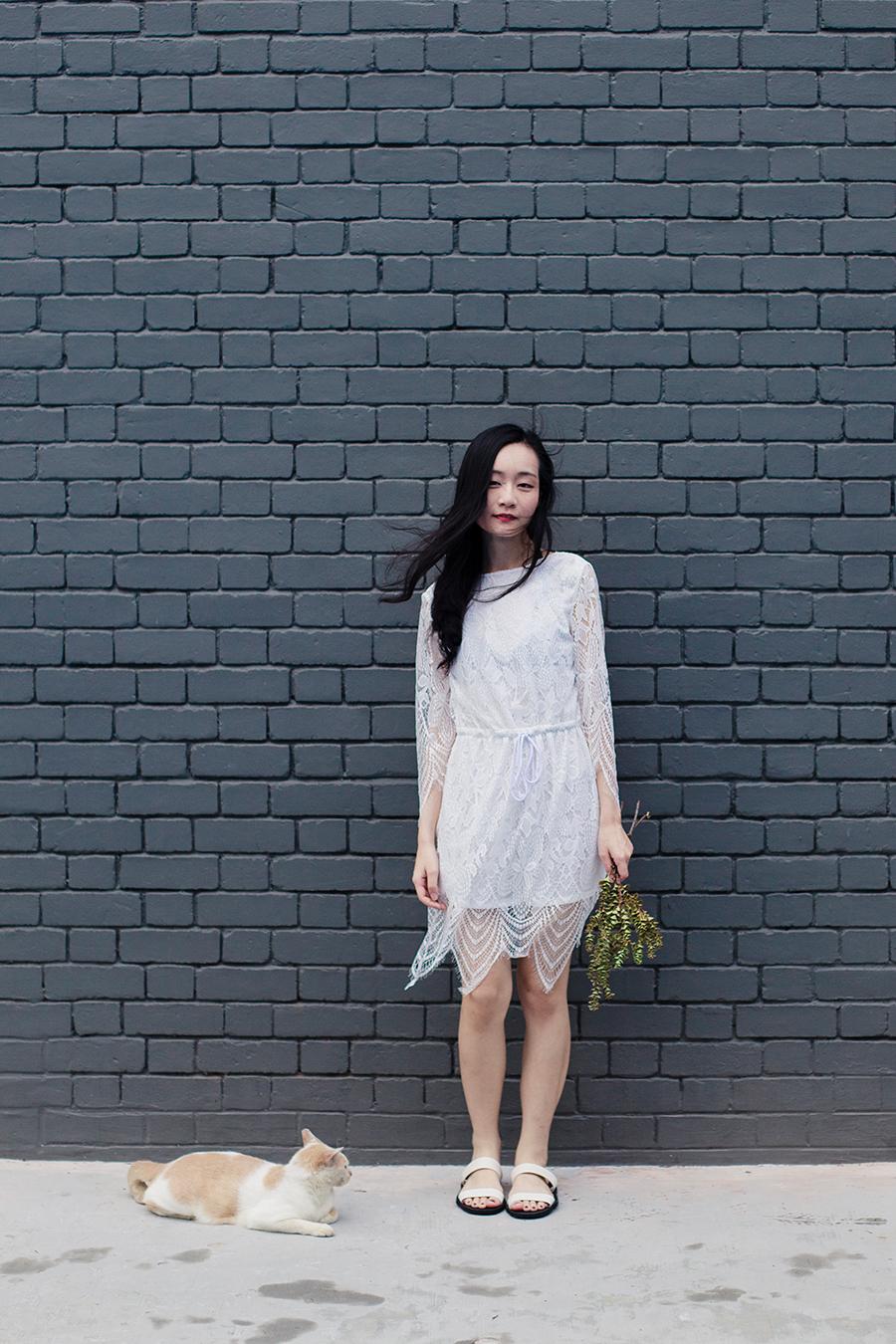Dresslink white backless lace romper, Dresslink black strappy cutout bralette, BlackOut SG black and white sandals.