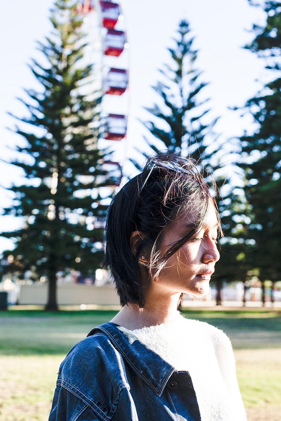 Windswept portrait in front of a ferris wheel in Fremantle Australia.