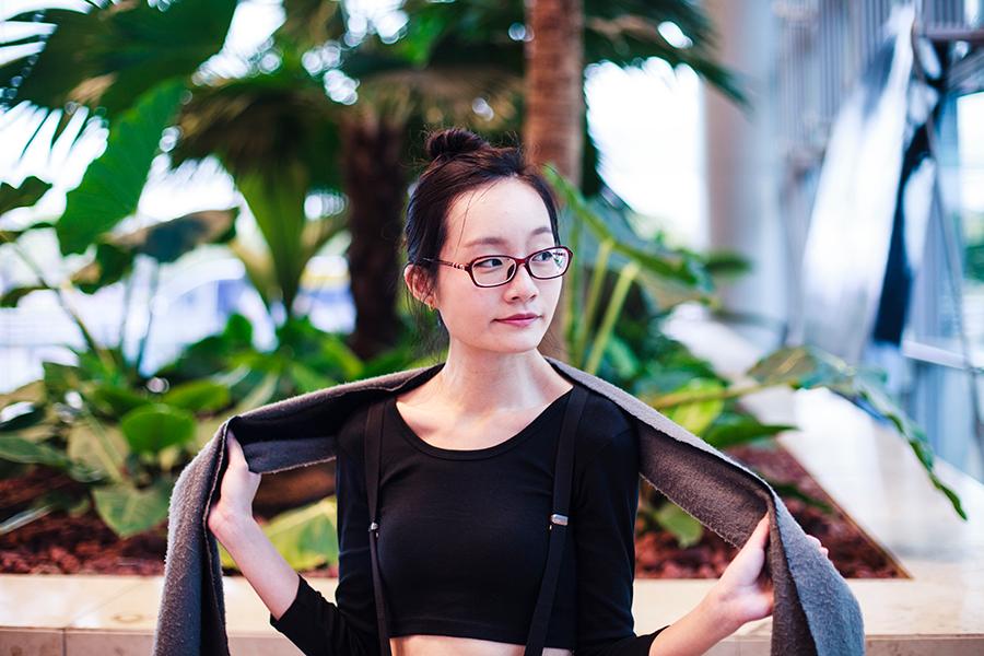 Black monochrome outfit for traveling: Dresslink black crop top, black elastic suspenders, Gap black framed glasses.