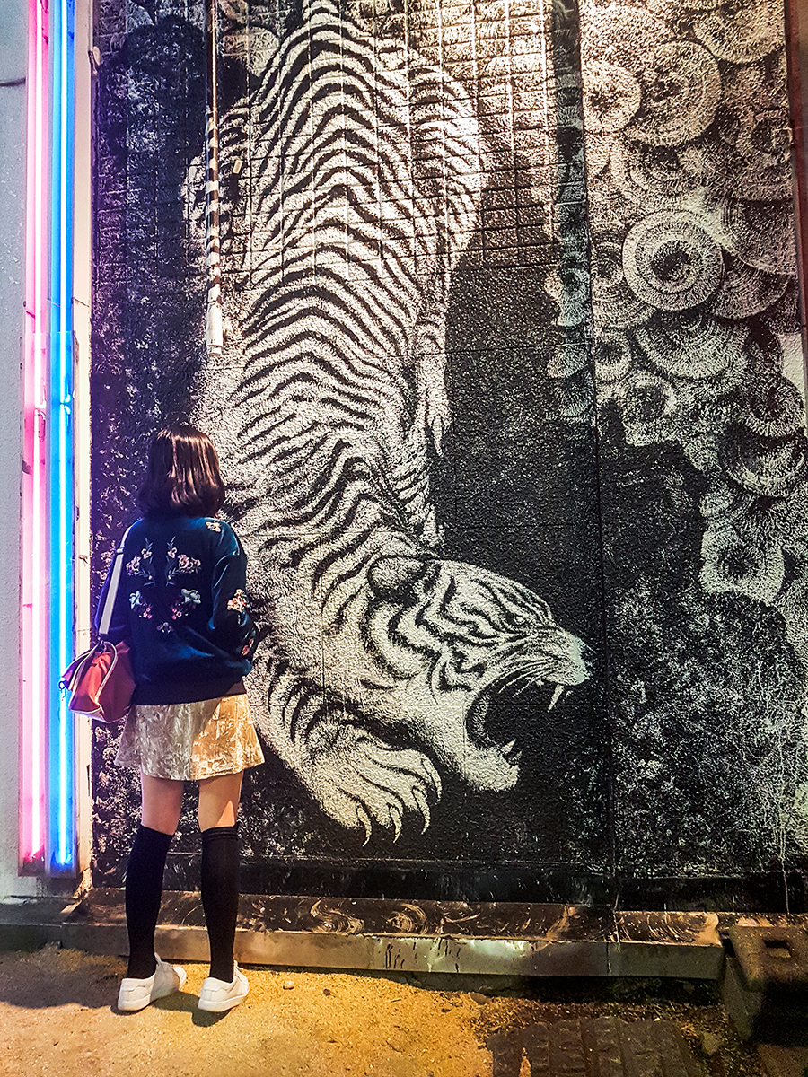 Embroidered Gamiss bomber jacket. Standing in front of a white tiger mural in Kabukicho, Tokyo.
