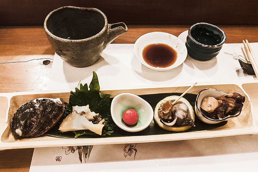 Platter of cold octopus topped with grated yuzu, welsh snail in a shell, small tomato, steamed abalone, and ornament in Makoto Sushi.