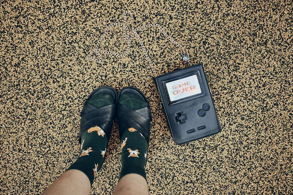 Puppy socks, black sandals, gameboy purse flatlay.