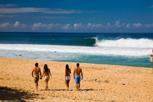 Couples watching surfers off a North Shore beach