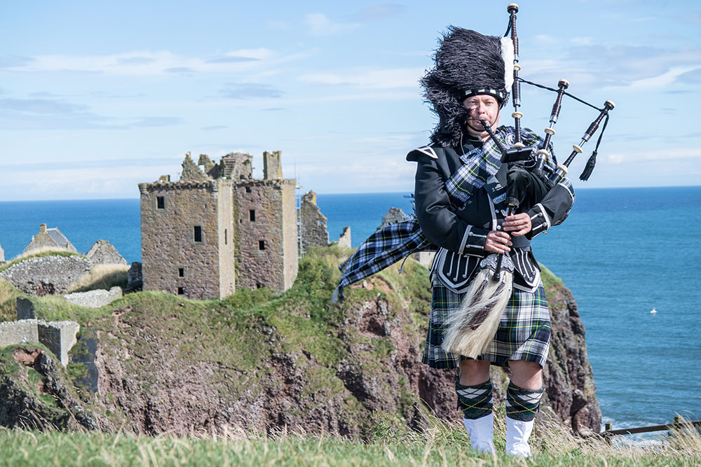 Traditional scottish bagpiper at Dunnottar Castle