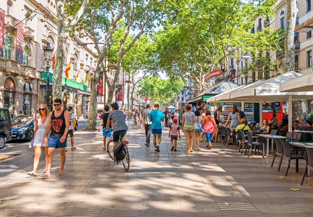 Hundreds of people promenading in the busiest street of Barcelona, the Ramblas.