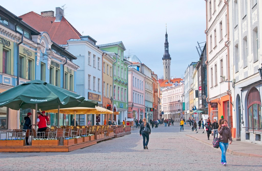 People walk on Viru Street. The street - is the main street of the Old Town. On the background is tower of Town Hall. Old Tallinn is part of the UNESCO World Heritage site