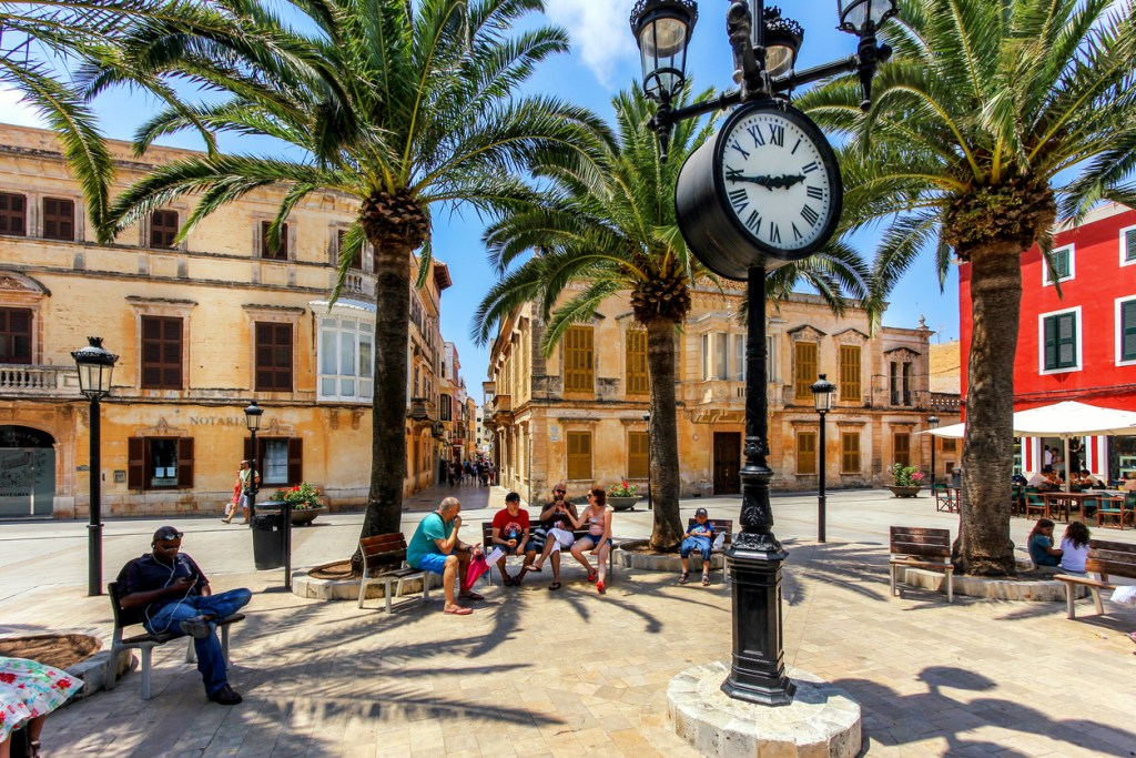 Tourists relaxing on Plaza Alfonzo III, at Ciutadella,  on the island of Menorca, Spain