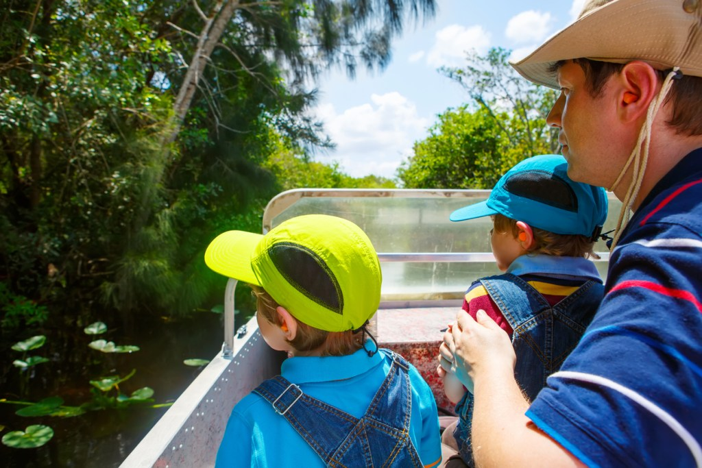 Two little kids boys and father enjoying air boat tour in Florida wetland swamp at Everglades National Park. Family, dad and children discovering wild nature and animals. Family having fun.