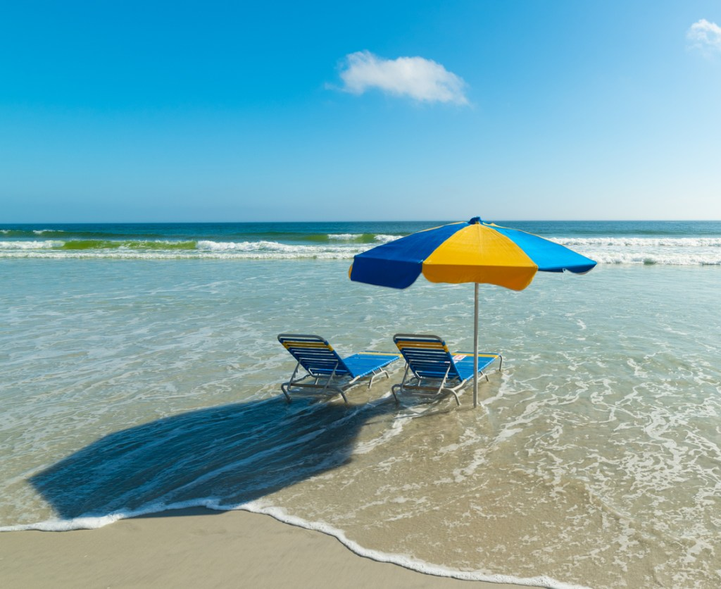 Beach chairs and beach umbrella in Daytona Beach. Florida, USA
