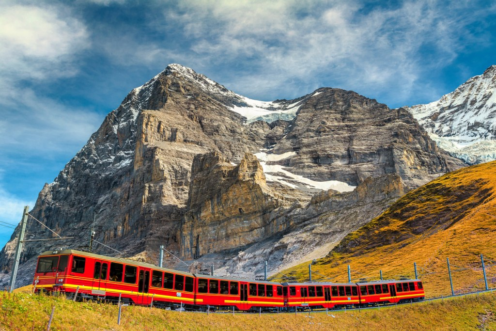 Famous express electric red tourist train coming down from the Jungfraujoch station (top of Europe) in Kleine Scheidegg tourist station, Bernese Oberland, Switzerland, Europe