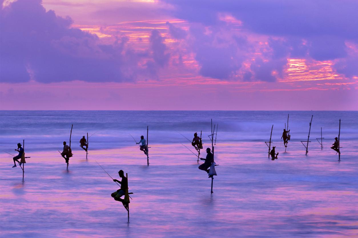 Fishermen on stilts in the silhouette at sunset in Galle, Sri Lanka
