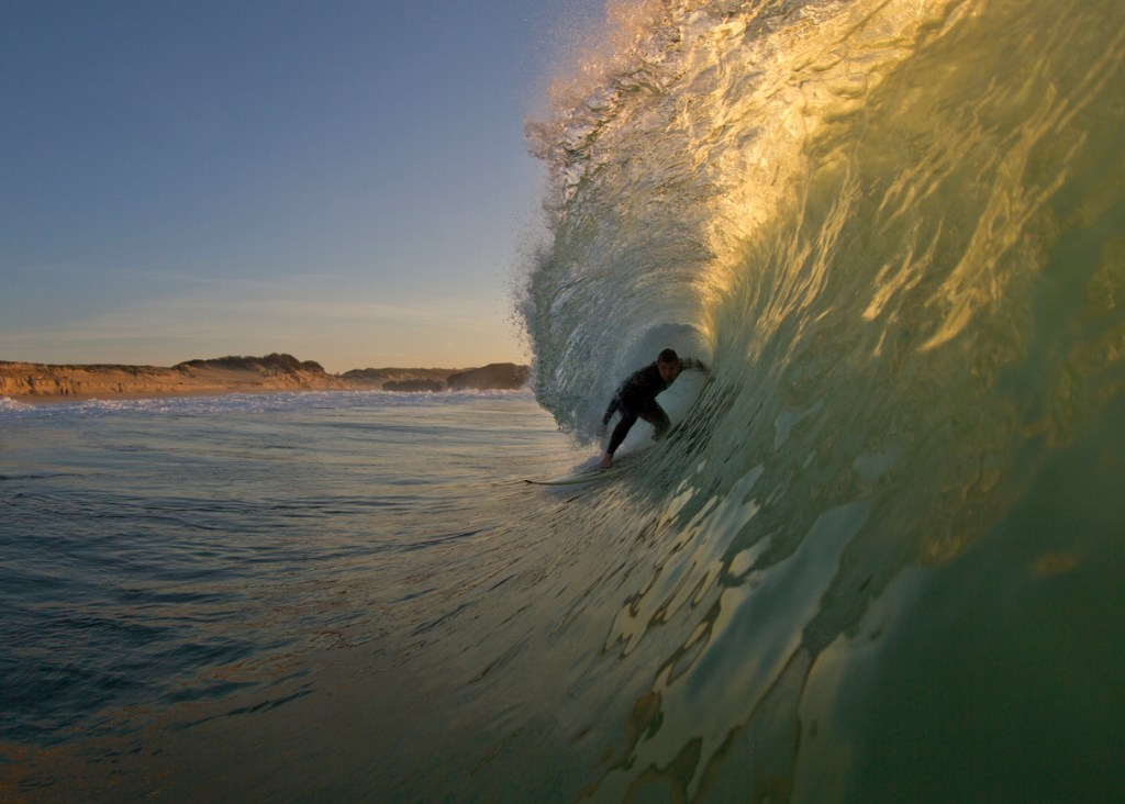 Surfer getting barreled in the afternoon light