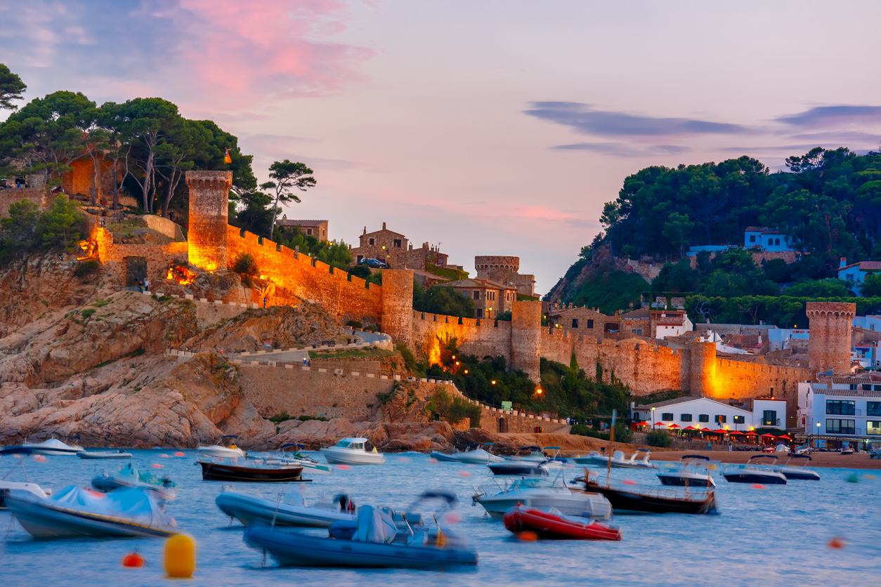 Fortress and fishing boats at Gran Platja beach and Badia de Tossa bay at sunset in Tossa de Mar on Costa Brava, Catalunya, Spain