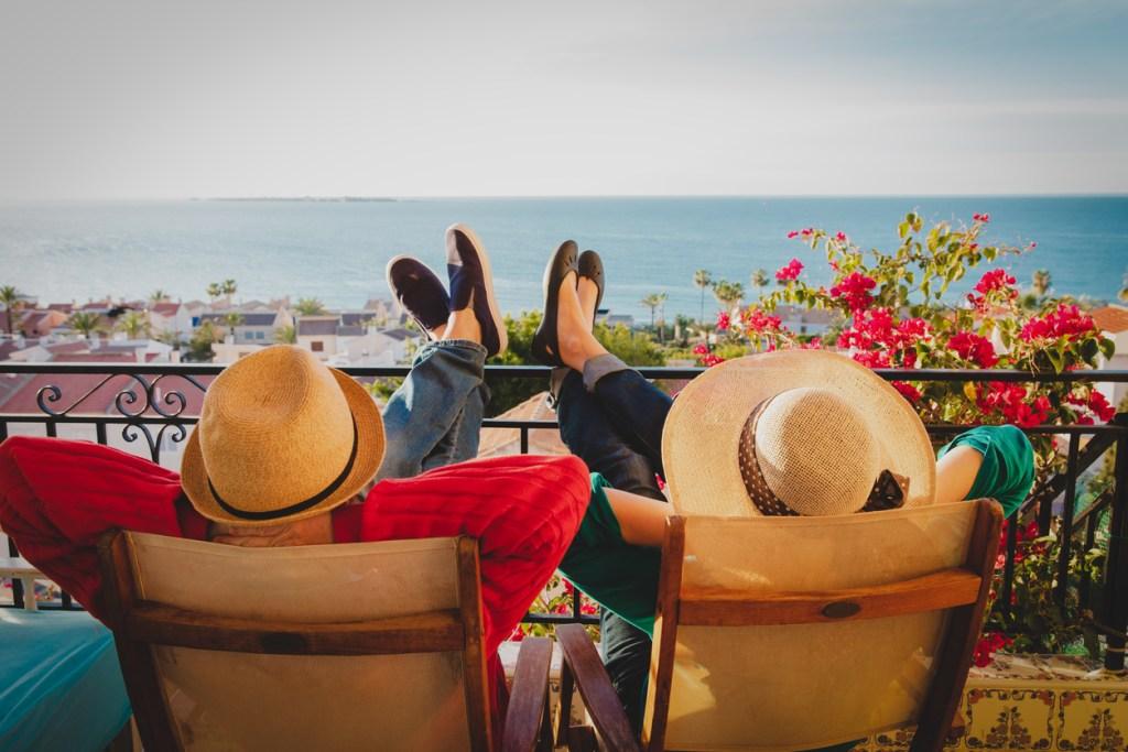 Happy couple relaxing on balcony terrace