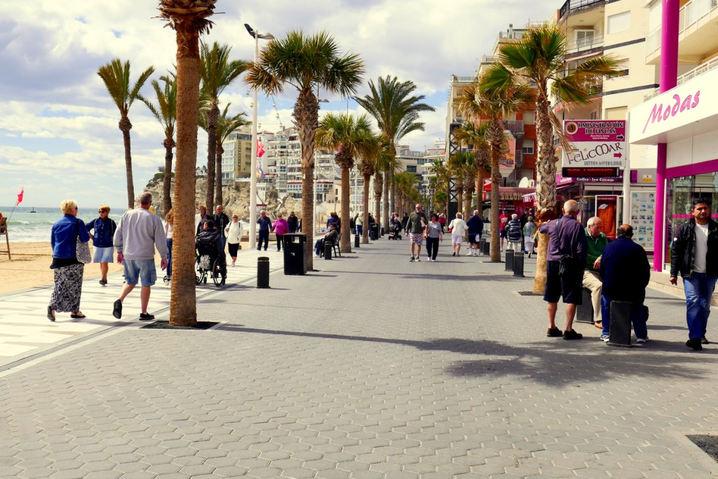 Holidaymakers and locals walking the Levante beach promenade in March at Benidorm on the Costa Blanca in Spain.