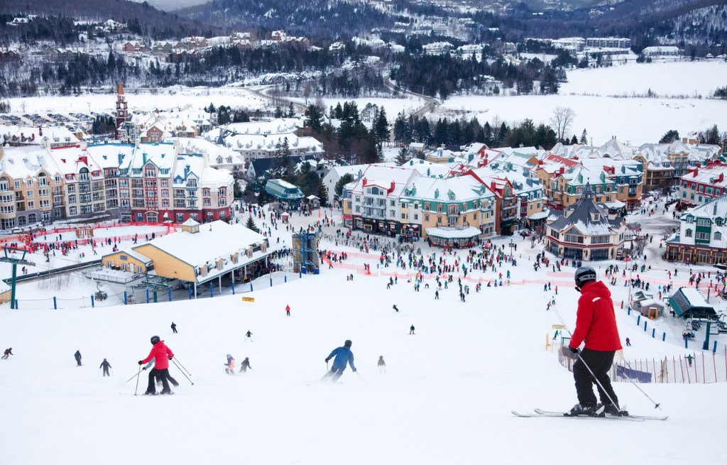 Skiers and snowboarders are sliding down the main slope at Mont-Tremblant. Mont-Tremblant Ski Resort is acknowledged by most industry experts as being the best ski resort in Eastern North America.