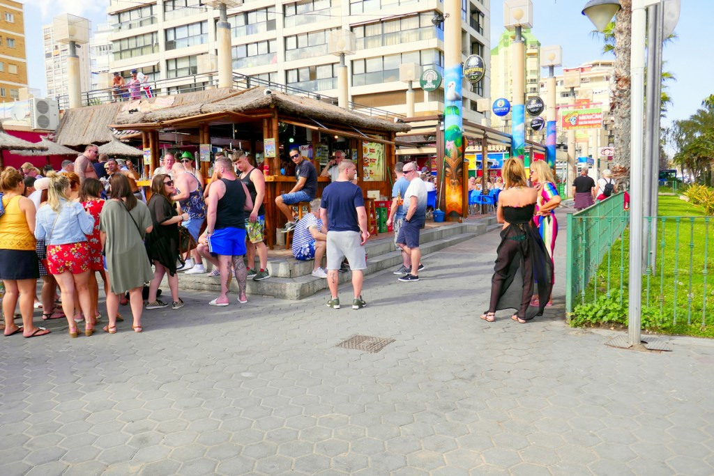 Holidaymakers gather for social food and drinks during the daytime at the Tiki beach bar on the promenade at Benidorm on the Costa Blanca in Spain.