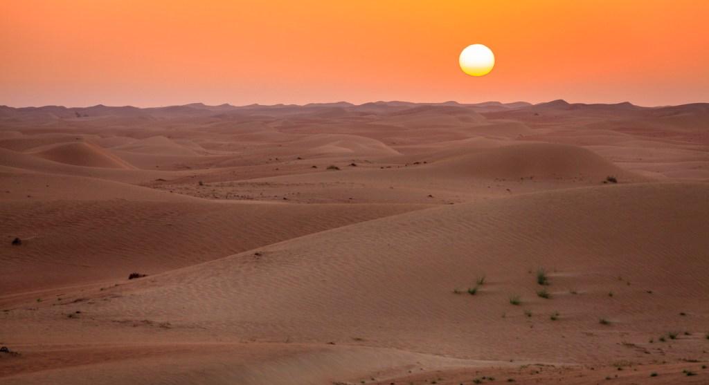 Sun rising over dunes of Dubai Desert Conservation Reserve, UAE
