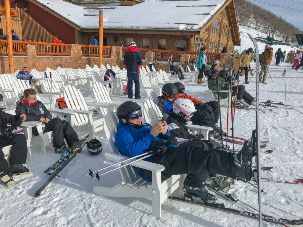 Skiers are sittting on chairs outside of Silver Lake lodge at Deer Valley resort.