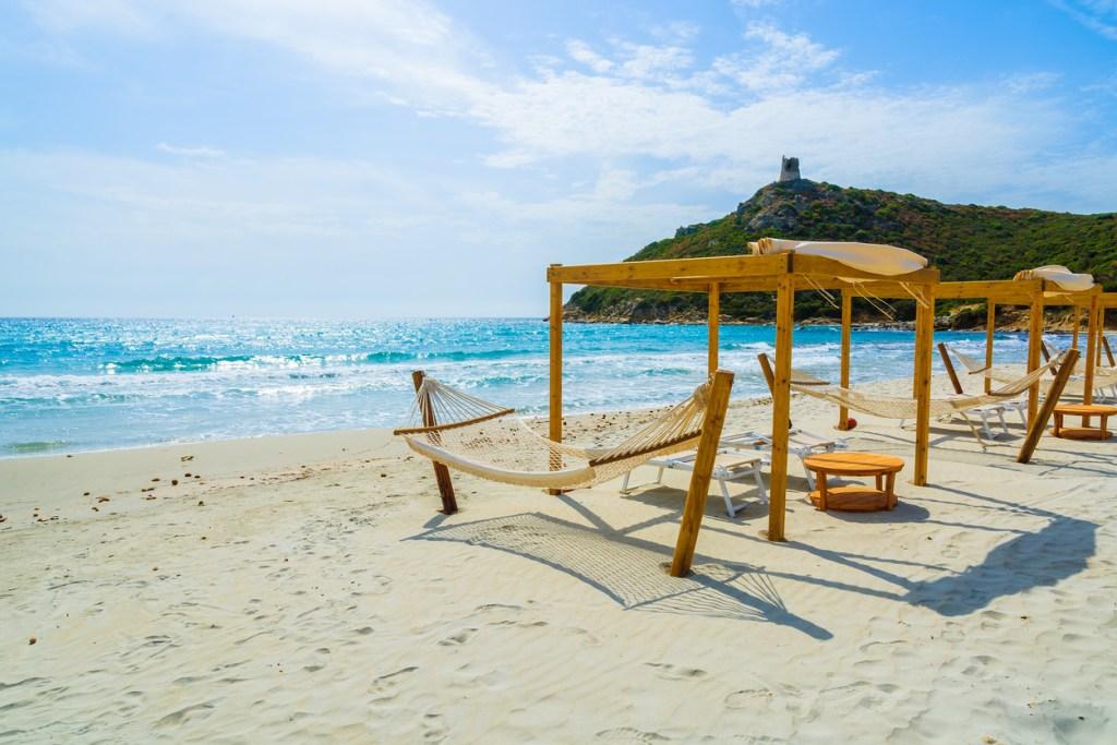 Hammocks and sun chairs on beach in Porto Giunco, Villasimius, Sardinia island, Italy